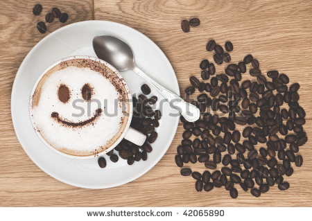 perle_positivita_stock-photo-cappuccino-coffee-with-smiley-face-on-wooden-table-overhead-view-42065890