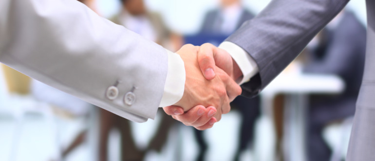 Two successful businessman shaking hands in front of corporate team at office